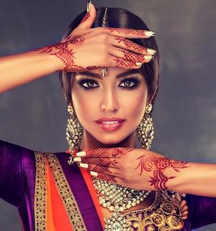 Портрет молодой индийской женщины с татуировками хной менди на руках и ярким макияжем