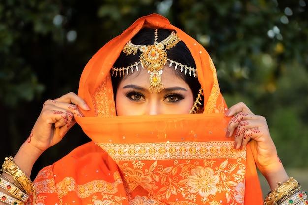 Портрет молодых индийских женщин с цветным лицом празднует фестиваль цветов холи.
