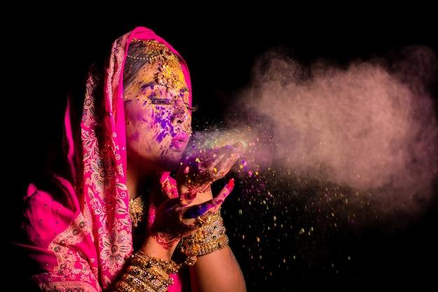 Holi 색상 축제를 축하하는 색상 얼굴로 젊은 인도 여성의 초상화.