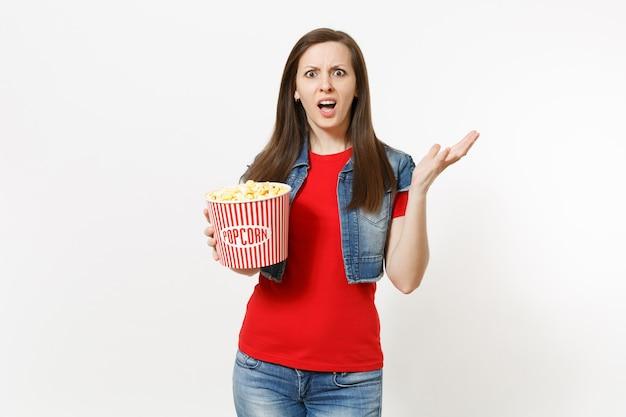 캐주얼 옷을 입고 영화 영화를 보고, 팝콘 양동이를 들고 흰색 배경에 격리된 손을 펼치고 있는 불만스러운 젊은 브루네트 여성의 초상화. 영화 개념의 감정.