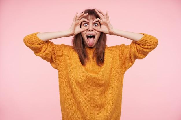 マスタードウールのセーターでピンクの壁の上に立っている間、彼女の舌を突き出し、彼女の目に上げた手を維持している若いうれしそうなブルネットの女性の肖像画