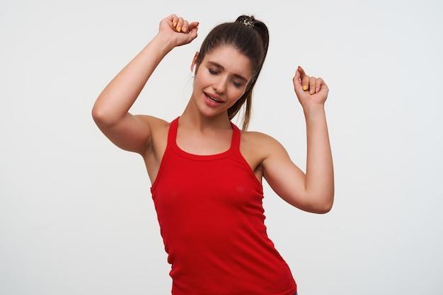 Портрет молодой радостной брюнетки носит красную футболку, слушает любимую песню в наушниках, поет и танцует с закрытыми глазами, стоит на белом фоне.