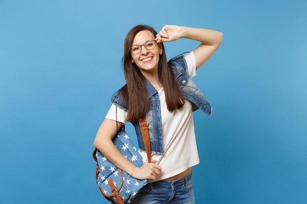 白いtシャツ、メガネを保持しているバックパックとデニムの服を着た若いうれしそうな面白いスマートな女性の学生の肖像画は、青い背景で隔離されます。高校大学カレッジコンセプトの教育。