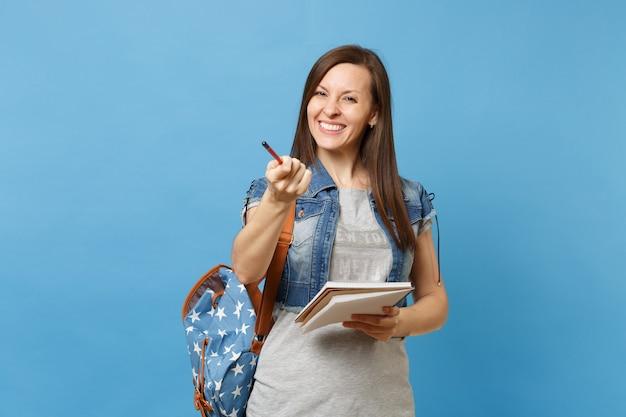 파란색 배경에 격리된 카메라에 연필을 가리키는 배낭 들고 노트북을 들고 데님 옷을 입고 웃고 있는 젊은 여학생의 초상화. 고등학교 대학 대학 개념의 교육입니다.