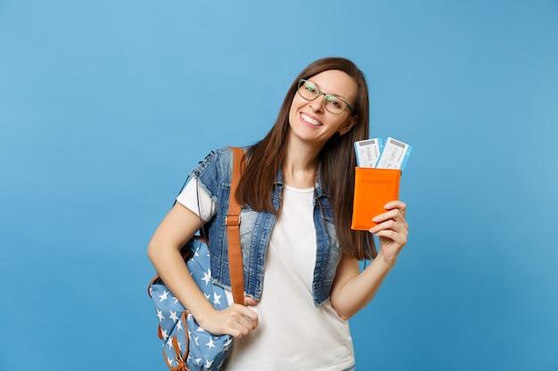 Портрет молодой радостной женщины-студента в очках с рюкзаком, держащим паспорт, билеты на посадочный талон, изолированные на синем фоне. обучение в вузе за рубежом. концепция полета авиаперелета.