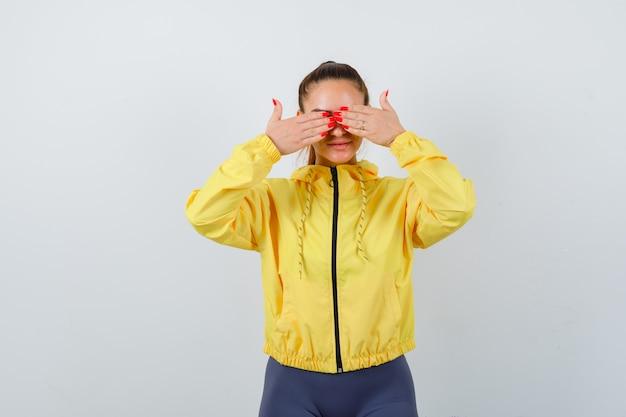 黄色いジャケットの手で目を覆い、怖い正面図を探している若い女性の肖像画