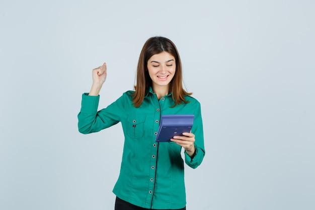 Портрет молодой леди, держащей калькулятор, показывающей жест победителя в зеленой рубашке и блаженной вид спереди