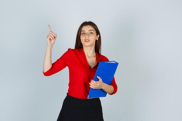 Портрет молодой леди, держащей папку, указывая вверх в красной блузке