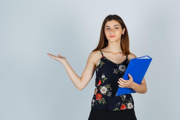 Портрет молодой леди, держащей папку, демонстрируя приветственный жест в блузке, юбке и уверенно выглядящей, вид спереди