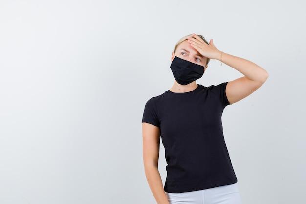 Tシャツ、ズボン、医療マスクで額に手を保持している若い女性の肖像画