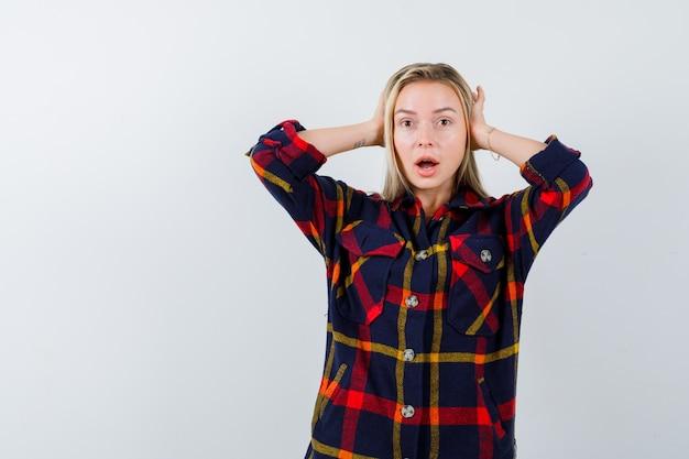 チェックのシャツで耳に手をつないで、困惑した正面図を見て若い女性の肖像画