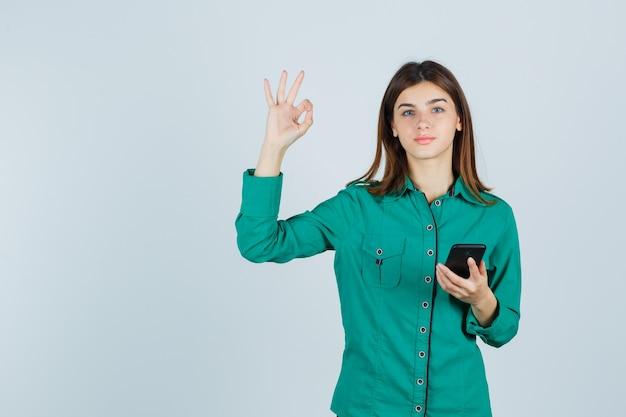 Портрет молодой леди, держащей мобильный телефон, показывающей жест в зеленой рубашке и довольной видом спереди