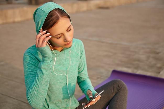 朝のヨガの後にヘッドフォンでお気に入りの曲を聴いて、明るいスポーツウェアの若い女性の肖像画。