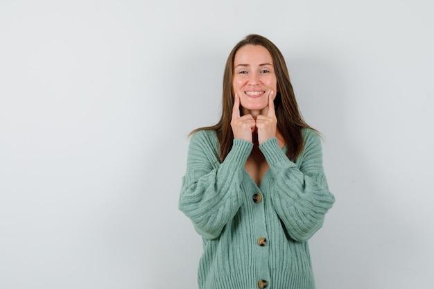 ウールのカーディガンで頬に指を保ち、嬉しい正面図を見て若い女性の肖像画