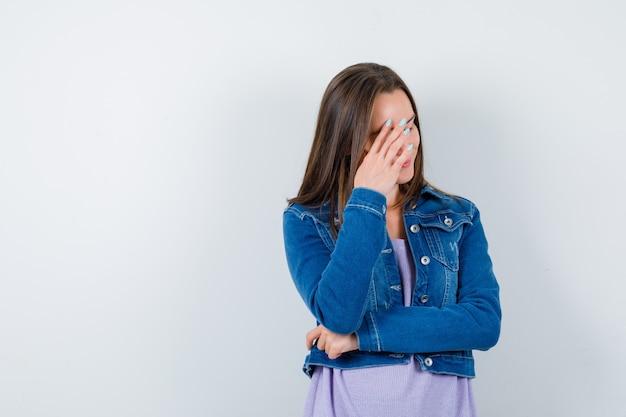 티셔츠, 재킷을 입고 얼굴에 손을 대고 부끄러워하는 앞모습을 바라보는 젊은 여성의 초상화