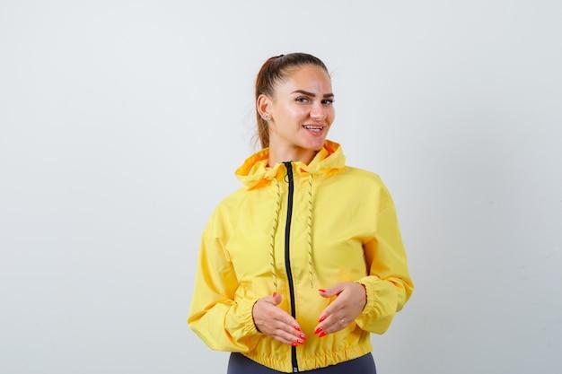 黄色いジャケットで彼女の前に手を保ち、楽観的な正面図を探している若い女性の肖像画