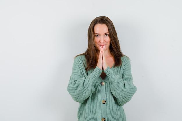 ウールのカーディガンで祈りのジェスチャーで手を保ち、希望に満ちた正面図を探している若い女性の肖像画