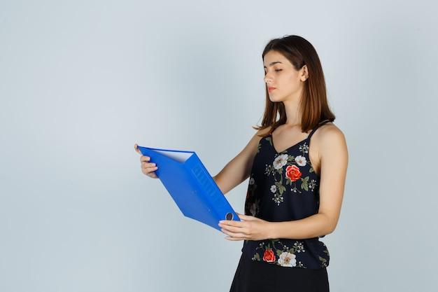 Портрет молодой женщины, смотрящей на папку в блузке, юбке и смотрящей сфокусированным видом спереди