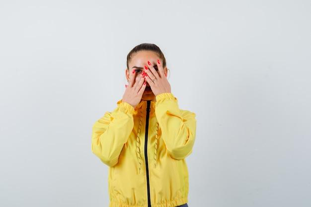 노란색 재킷을 입은 손가락을 들여다보고 긍정적인 정면을 바라보는 젊은 여성의 초상화