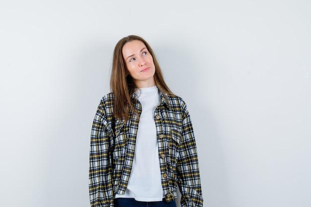 Портрет молодой леди, глядя вверх в футболке, куртке и глядя вдумчивый вид спереди