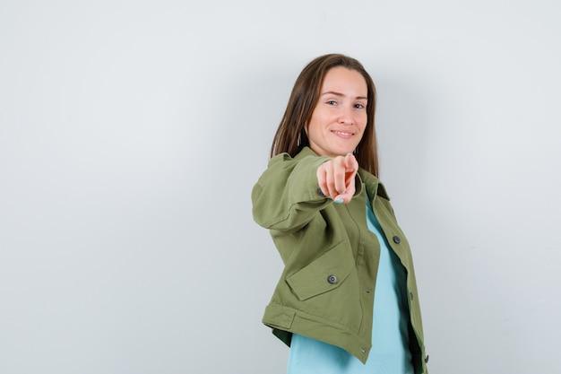 Портрет молодой леди, указывая на камеру в футболке, куртке и весело глядя спереди