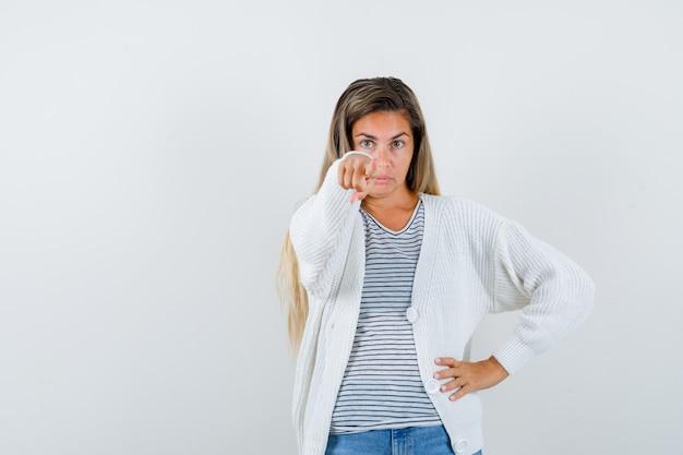 Портрет молодой леди, указывая на камеру в футболке, куртке и любопытно глядя спереди