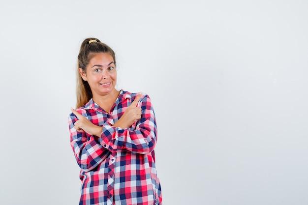 チェックのシャツを着て、陽気な正面図を見て若い女性の肖像画
