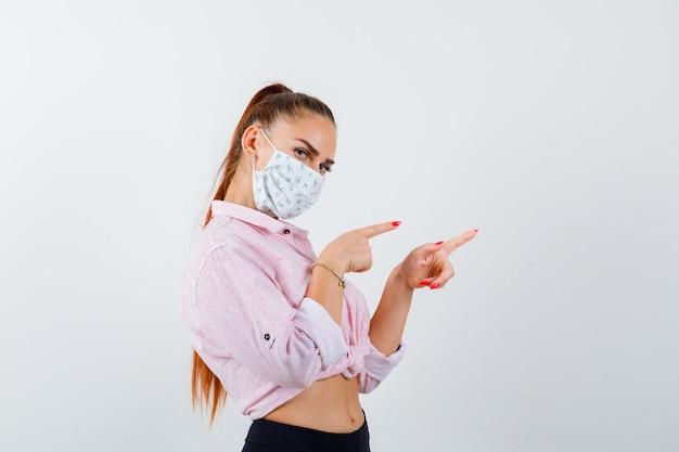 Портрет молодой женщины, указывающей вправо в рубашке, маске и уверенно выглядящей вид спереди