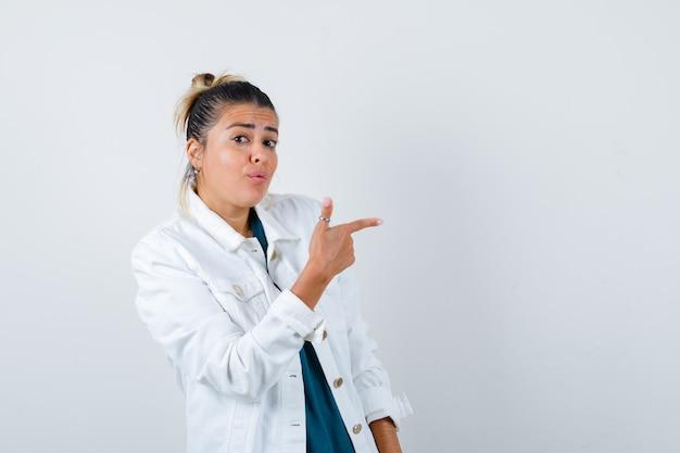 白いジャケットを右に向けて、不思議な正面図を見ている若い女性の肖像画