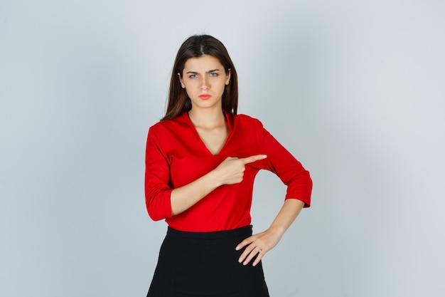 Портрет молодой леди, указывающей на правую сторону в красной блузке