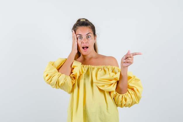 Портрет молодой леди, указывающей на правую сторону в желтом платье и выглядящей изумленным видом спереди