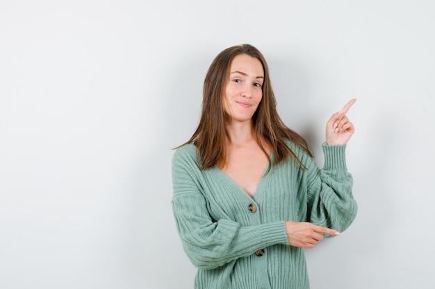 ウールのカーディガンで上向きと右向きで陽気な正面図を探している若い女性の肖像画