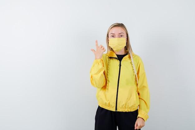 トラックスーツ、マスク、困惑した正面図で上向きの若い女性の肖像画