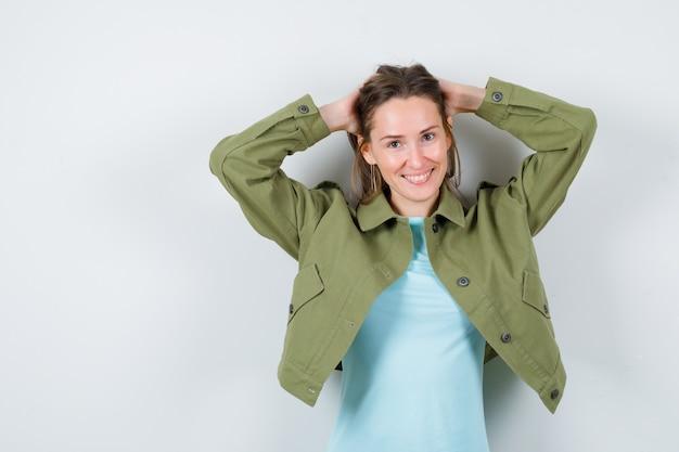 Портрет молодой дамы позирует, укладывая волосы в футболку, куртку и выглядя великолепно, вид спереди