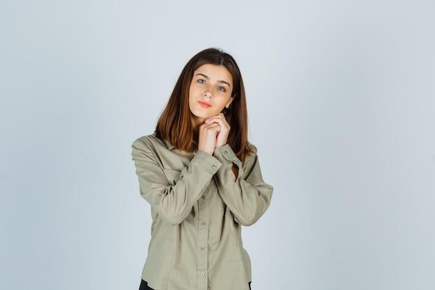 シャツの握りしめられた手にあごを支え、賢明な正面図を探している若い女性の肖像画