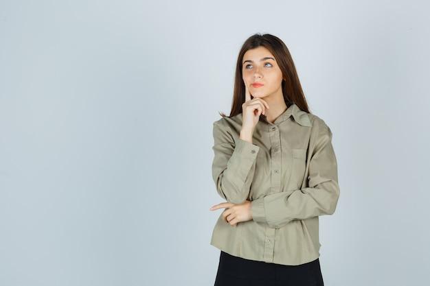 Портрет молодой женщины, подпирающей подбородок рукой, держащей палец за щеку в рубашке, юбке и задумчивой смотрящей спереди