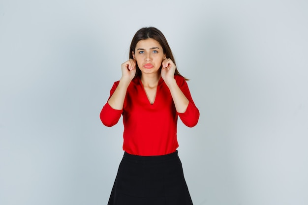 Портрет молодой дамы, дергающей мочки ушей в красной блузке, юбке и обиженной