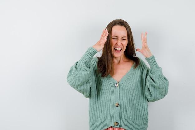 Портрет молодой леди, поднимающей руки, крича в шерстяном кардигане и возбужденного вида спереди
