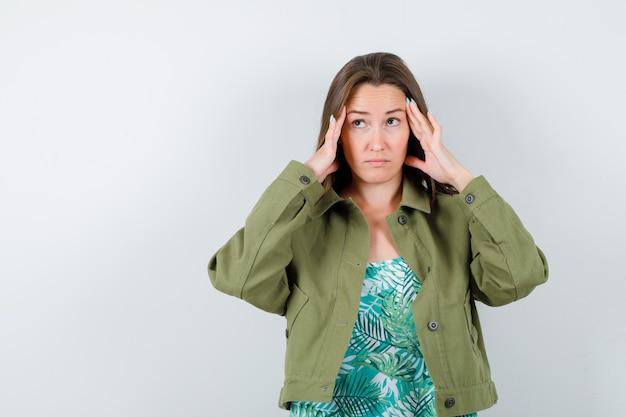 녹색 재킷에 관자놀이를 문지르고 사려깊은 정면을 바라보는 젊은 여성의 초상화