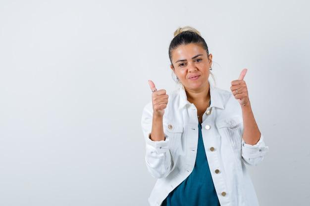흰색 재킷에 두 엄지 손가락을 표시하고 기쁘게 전면보기를 찾고 젊은 아가씨의 초상