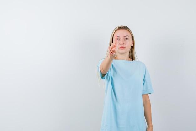 보여주는 젊은 아가씨의 초상 t- 셔츠에 잠시 제스처를 잡아