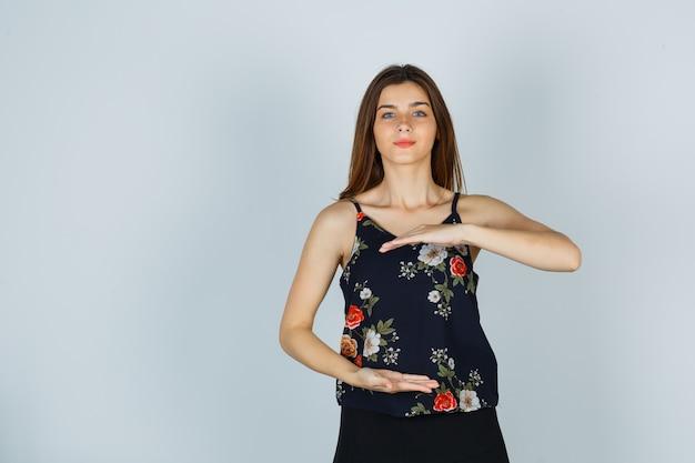 Портрет молодой женщины, показывающей знак большого размера в блузке, юбке и уверенно выглядящей вид спереди