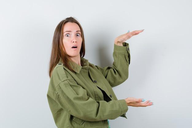 緑のジャケットで大きなサイズのサインを示し、ショックを受けた正面図を見て若い女性の肖像画