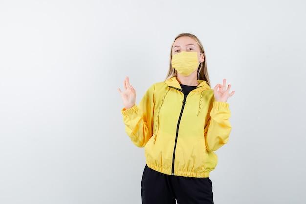 トラックスーツ、マスク、誇らしげな正面図でokジェスチャーを示す若い女性の肖像画