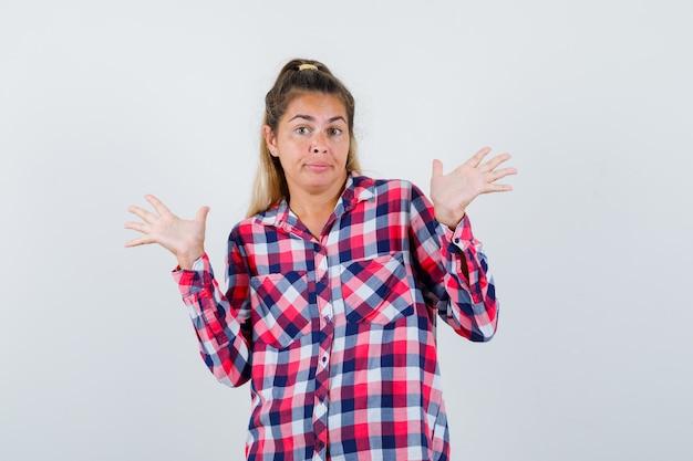 チェックシャツで降伏ジェスチャーで手のひらを示し、混乱した正面図を見て若い女性の肖像画