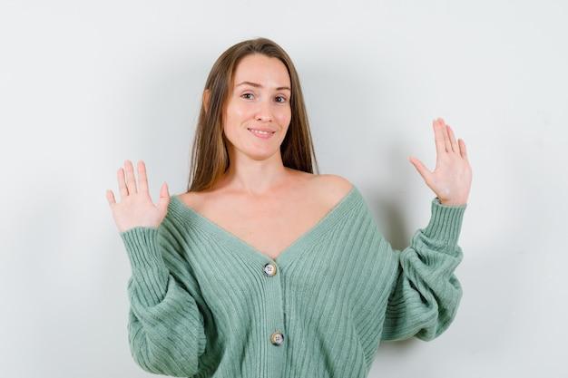 ウールのカーディガンで降伏ジェスチャーで手のひらを示し、自信を持って正面を見る若い女性の肖像画