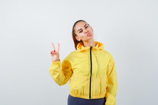 平和のジェスチャーを示し、トラックスーツで唇をふくれっ面し、自信を持って正面を見る若い女性の肖像画