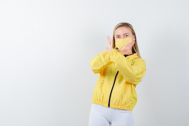 ジャケット、ズボン、マスクで拒否ジェスチャーを示し、自信を持って正面を見る若い女性の肖像画