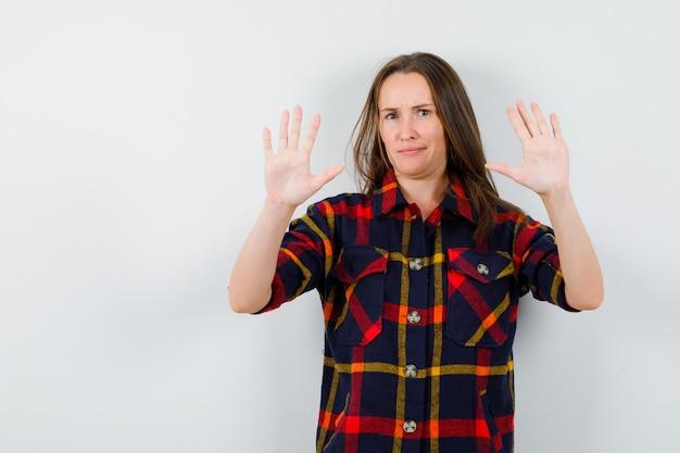 カジュアルなシャツで停止ジェスチャーを示し、断固とした正面図を見て若い女性の肖像画