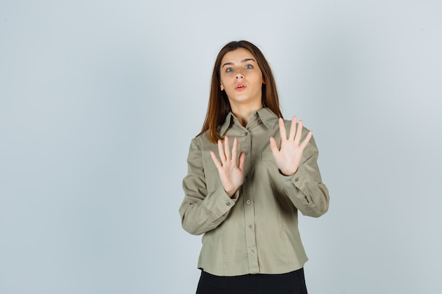 シャツ、スカート、怖い正面図で停止ジェスチャーを示す若い女性の肖像画